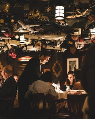 Guests at tables in a dark-lit restaurant with an eclectic collection of ceiling ornaments