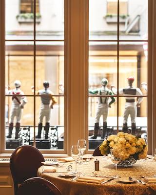 Una mesa de cena formal junto a una gran ventana rodeada de figuritas de jinetes