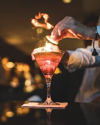 Primo piano di un cocktail rosa illuminato dalle fiamme che viene appoggiato su un tavolo
