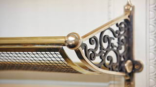 Close-up of a brass luggage rack with ornate ironwork detailing