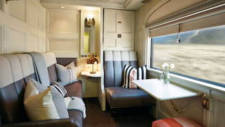 Light and airy train cabin with a leather banquette sofa and chair with table