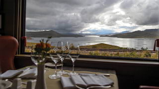 View through a window from a luxury train dining table of a lake among mountains