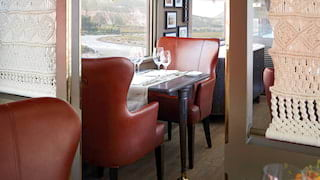 Two burgundy leather chairs at a dining car table next to a large window