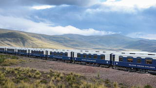A line of blue and white carriages curving through a lush green valley