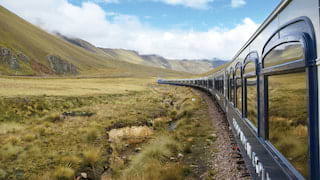 Row of train windows reflecting the lush Andean plains trackside