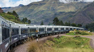 Blue and white train carriages curving under a cloud-coated Andean mountain