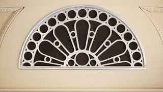 Close-up of a white, ornate, wrought-iron ventilation grate in a fan formation