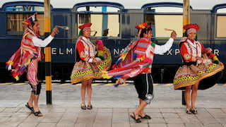 Four Peruvian dancers in traditional dress whirling on a train platform