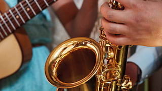 Close-up of hands tapping the keys of a shiny brass saxophone
