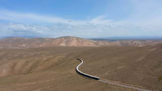 Long distance aerial view of a train snaking across a vast Andean plain