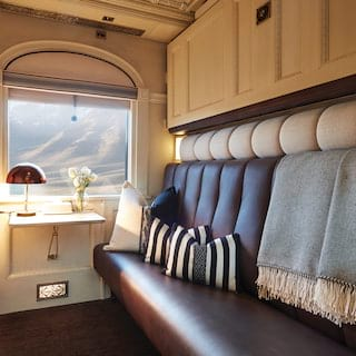 Train cabin with a leather banquette seat and arched window with Andean views