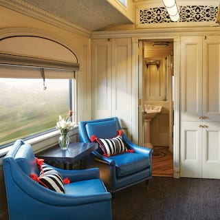 Train cabin suite with light cream decor and vibrant blue leather armchairs