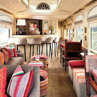 Elegant train bar car with imprinted leather chairs and vibrant Peruvian fabrics
