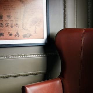 Close-up of a deep burgundy leather chair next to a sage-coloured wall panel