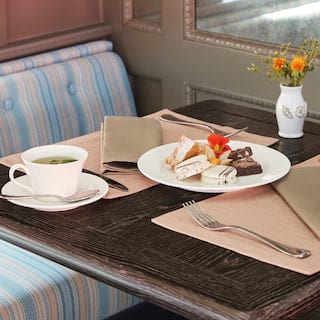 Close-up of a train dining car table with a cup of tea and cake platter on top