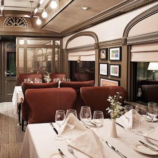 Tables for four lining a lamplit train dining car set for a formal dinner