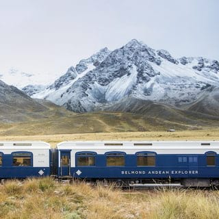 Two white and navy train carriages before snow coated Andean mountains