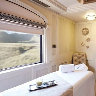 Bright train spa carriage with a massage table next to a large picture window
