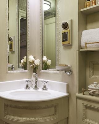 Train cabin bathroom with white tiles, light sage walls and curved corner sink