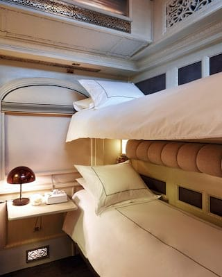 Lamplit train cabin with bunk beds and elegant cream and beige accents