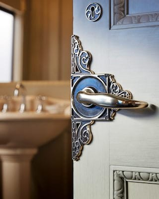 Close-up of an ornate brass door handle on an open door to an en-suite bathroom