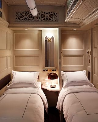 Two twin beds side-by side in a lamplit train cabin with light elegant decor