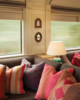 Close-up of a train bar car with tweed sofas and Peruvian print cushions