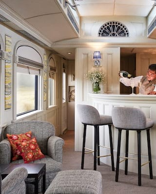 Barman in a train bar car pouring champagne into a flute glass