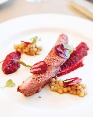 Close-up of a beef carpaccio garnished with chickpeas