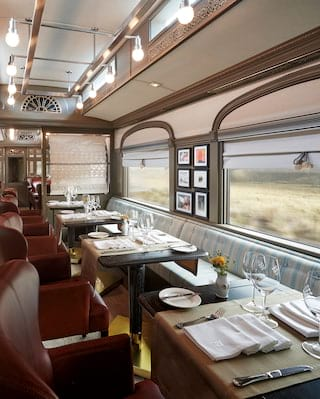 Dining car with burgundy leather armchairs and banquette seating against the wall
