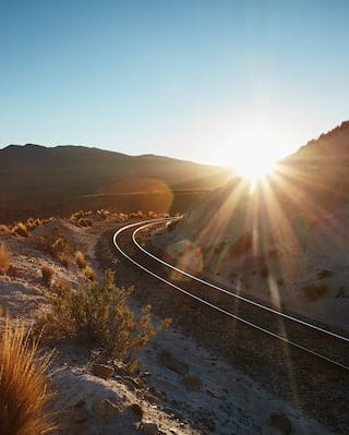 Sun bursting from behind two mountains to shine on curving train tracks