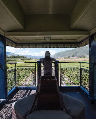 Open-air train observation deck, lined with ornate colonial-style iron railings