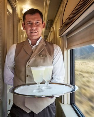 Train steward in beige waistcoat holding two pisco sour cocktails on a silver tray