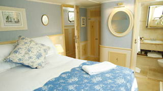 Barge cabin with powder blue walls and a blue floral bedspread on a large bed