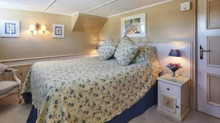 Vast pillowy bed with a blue and yellow floral bedspread in a bright lamplit cabin