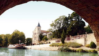 River barge moored beside a medieval French village viewed through a stone arch