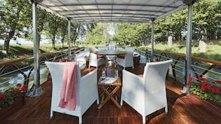 White wicker deck chairs under a white canopy on a polished wooden boat deck