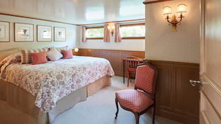 Spacious barge cabin with a red toile-patterned bedspread and matching cushions