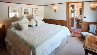 Vast bed with a mint green-patterned bedspread in a spacious barge cabin