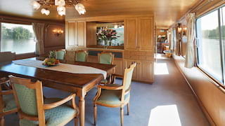 Dining area on a luxury barge with a mahogany table and elegant matching chairs