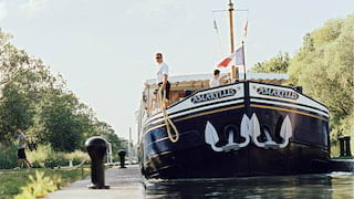 Bow of a dark navy river barge with a gold stripe mooring alongside a leafy canal