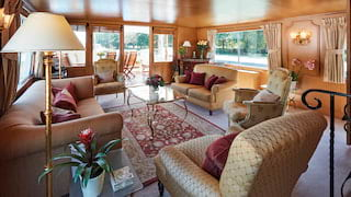 Walnut wood-panelled lounge area of a river barge with plush baroque-style seating