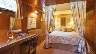 Lamplit four-poster bed with classic gold toile drapes in a wood-panelled cabin