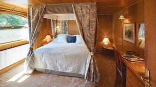 Sunlight-filled wood-panelled cabin with a plush four-poster bed and toile drapes