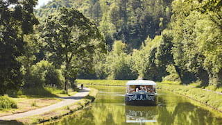 Navy blue river boat with a white canopy sailing along a rural canal on a sunny day