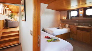 View through an open door of a double cabin with two single beds and a sink unit