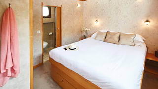 Plush king-bed in a luxurious river barge cabin with silver floral wallpaper