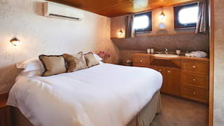 Pillowy bed in a luxurious river barge cabin with gleaming wood-panelled ceiling