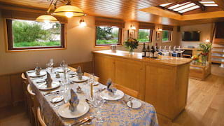 Formal dining area of a luxury barge with a patterned satin tablecloth and napkins