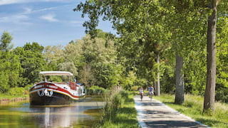 Black bottomed river barge with a red stripe drifting down a tree-lined canalside